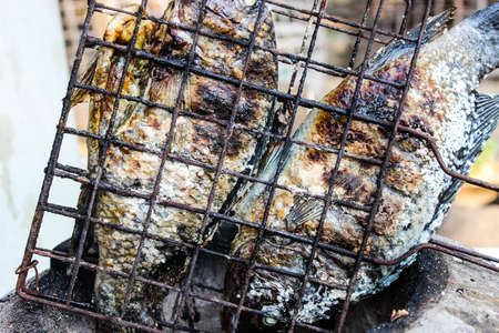Two grilled fish that are cooked and eaten