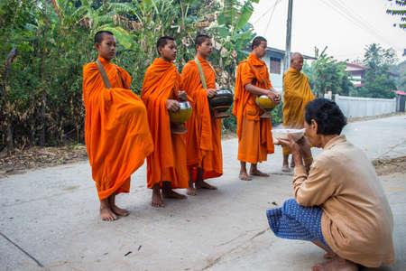 SURIN THAILANDIA-21 gennaio la donna non identificato dare cibo ai monaci e offrendo cibo ai monaci in Thailandia Editoriali
