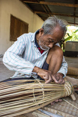 Surin, Thailand -9 January  Unidentified man doing with a machine woven bamboo fishing equipment  The machine woven bamboo crafts of Thailand farmers  On January 9, 2013  Surin, Thailand