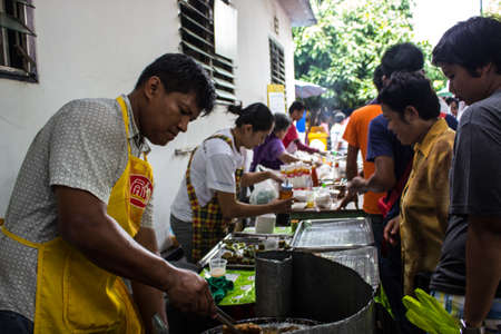 SINGBURI, Thailandia-15 agosto: persone non identificate cucinare dolci fritti, gratuito per le persone che si uniscono l'anniversario dei compleanni padre Charan a AmpawanTemple il 15 agosto 2013 AmpawanTemple Phrom Buri quartiere Sing Buri Provincia, Thailandia