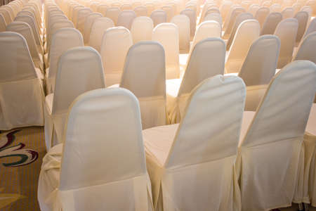 Chairs covered with white cloth, usually used for weddings Stock Photo