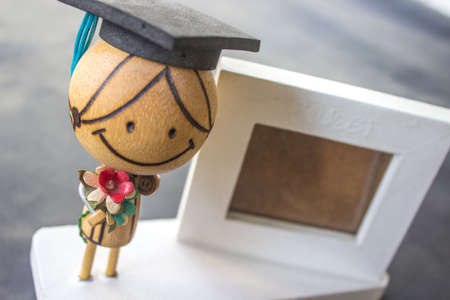 Wooden doll wearing a hat and holding flowers and white picture frame. Stock Photo