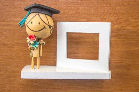 Doll cornice-bianco con uno sfondo in legno.