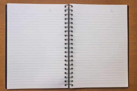 Open the notebook with a white face on the wood. Stock Photo