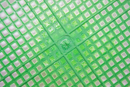 Green plastic basket texture as a background.