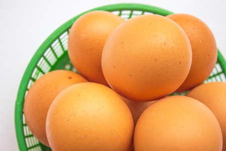 Brown uova nel paniere su bianco. Archivio Fotografico