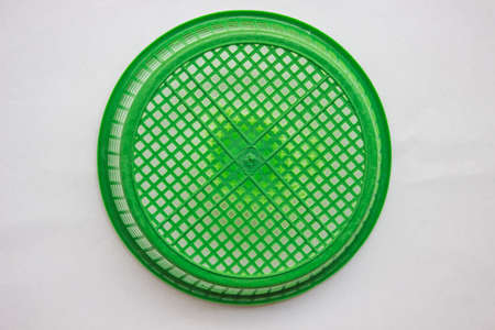 Green plastic basket on a white background.