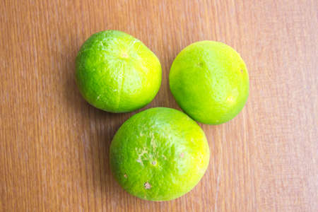 Fresh lemon three balls on a wooden background.