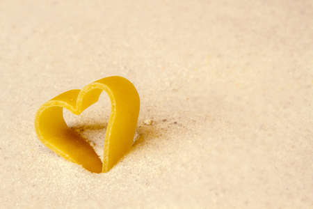 evoke: figure of a heart in the sand Stock Photo