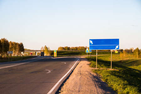 stay on course: road with sign pole and blue sky with clouds