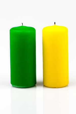 two candles of different colors on a white background photo