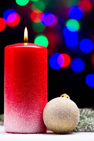 ate: two lighted candles, red and white with a branch ate in the beautiful bokeh
