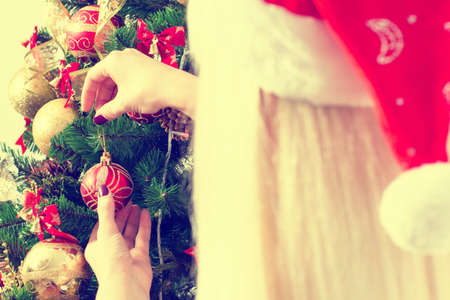 decorates: Woman decorates a Christmas tree different toys