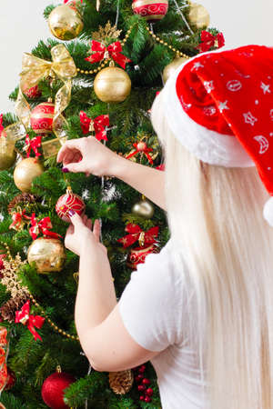 woman hanging toy: Woman hangs on the Christmas tree toys