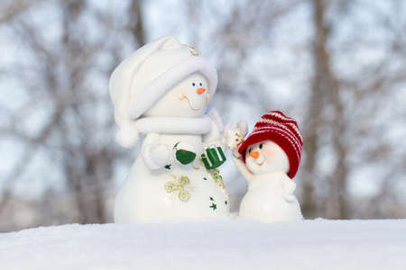 scarf beach: two snowmen in the snow, in little red cap looks at the large snowman Stock Photo