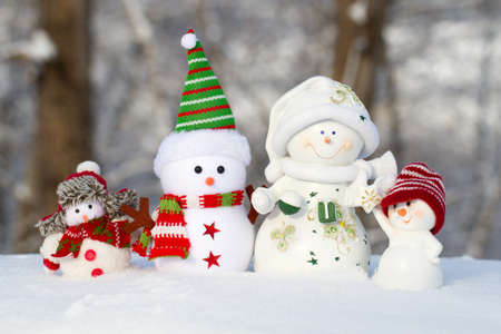 scarf beach: four snowmen on a snow stand in one row, two large and two small