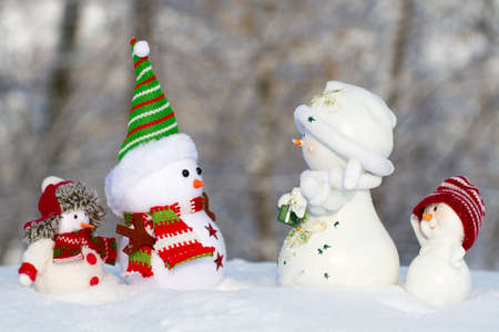 scarf beach: four snowman in the snow looking at each other, two large and two small