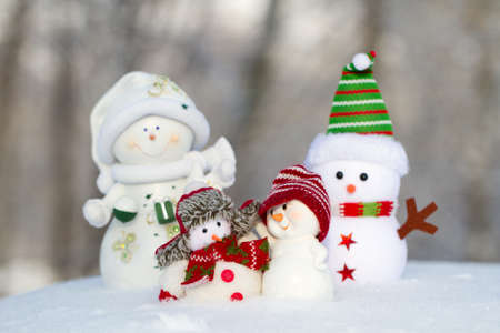 next to each other: four snowmen are standing next to each other in clothing