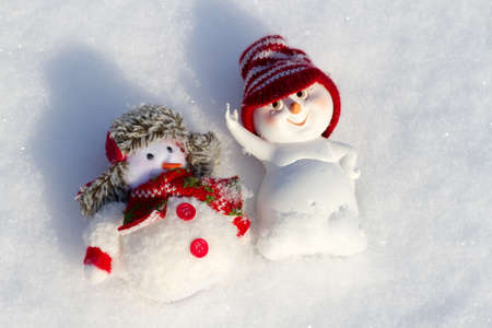 scarf beach: two Snowman lying on the snow - sunbathe