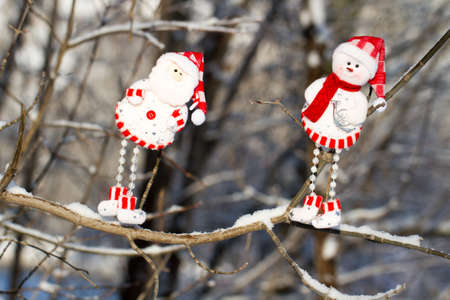 scarf beach: two cheerful snowman in hat and red scarf hanging on a branch, Santa Claus