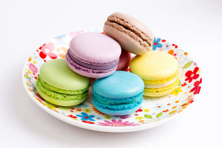 Collection of brightly colored French macarons on white background, lying in a saucer