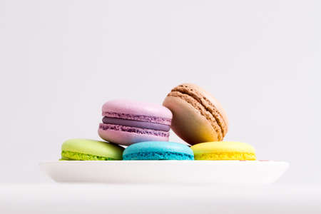 french bakery: Collection of brightly colored French macarons on white background, lying in a saucer