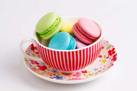 french bakery: Collection of brightly colored French macarons on white background, lying in a Cup Stock Photo