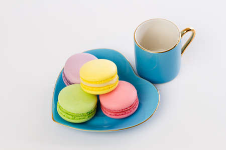 french bakery: collection of brightly colored French macarons are on a blue saucer the shape of a heart Stock Photo