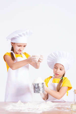 knead: Two girls knead the dough, on a white background Stock Photo