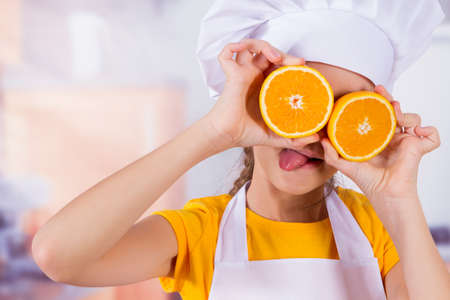 summer diet: Little girl playing with fresh Mandarin fruits, shows tangerine eyes