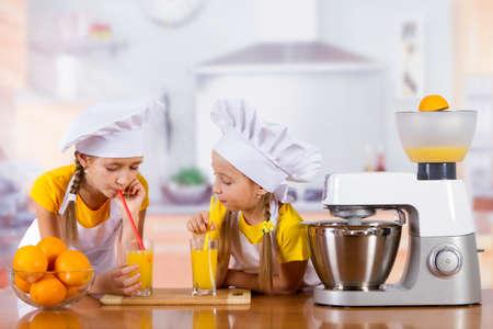 two girls drink fresh orange juice in the kitchen, standing next to a kitchen machine