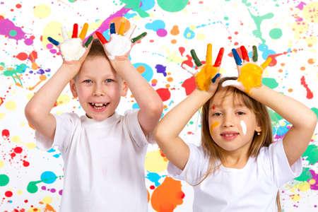 ni�os felices: ni�o y ni�a jugando con las flores, un ni�o y una ni�a muestra las manos pintadas