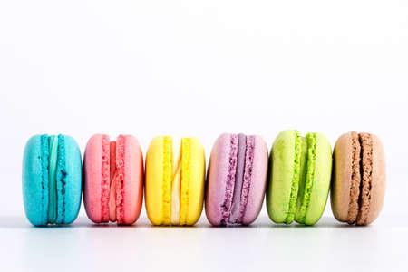 galletas: Macarrones franceses dulces y coloridos o macarrón en el fondo blanco, postre.