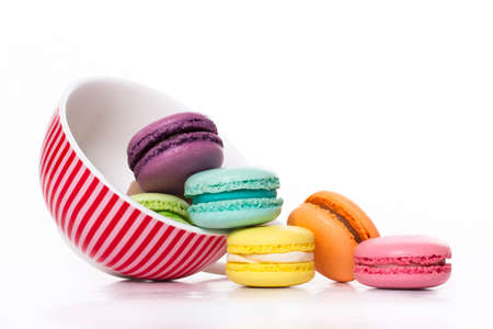 colorful macaroons lie in an upside-down mug, white background
