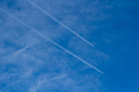 condensaci�n: A commercial airplane flying at high altitude leaving contrails or condensation trails against  blue sky. Foto de archivo