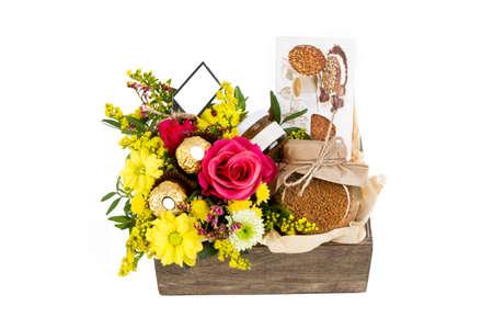 Anordnung für Blumen und Kaffee in einer Holzkiste auf einem weißen Hintergrund