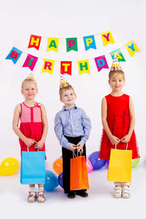 Children hold bags. Isolated on a white background, the inscription happy birthday Stock Photo