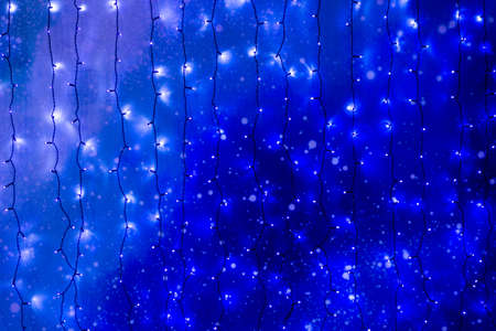 Christmas lights frame on dark blue background with copy space