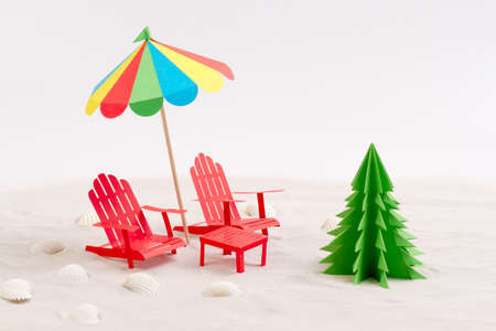made from paper christmas tree beach chair and umbrella in the sand white background - Umbrella Christmas Tree