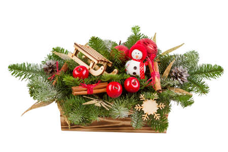 Christmas arrangement of fir branches, in wooden box, snowman with sled.