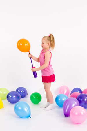 The little girl inflates the Balloon on the White Background Stock Photo