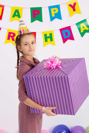 Girl holding a big box with a gift. Garland with the Inscription happy birthday. white background. Stock Photo