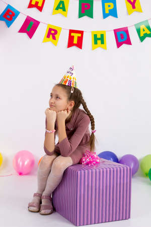 Sad girl is sitting with a gift. Garland with the Inscription happy birthday. white background. Stock Photo