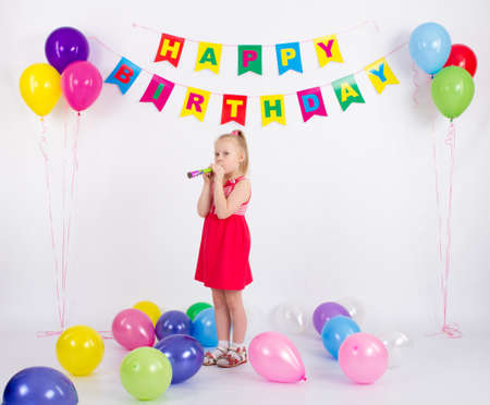 Girl holding a whistle stands next to balloons inscription happy birthday, white background Stock Photo