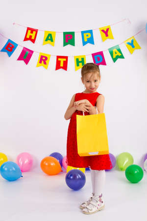 Girl holds in his hands package with a gift. The inscription happy birthday. Stock Photo