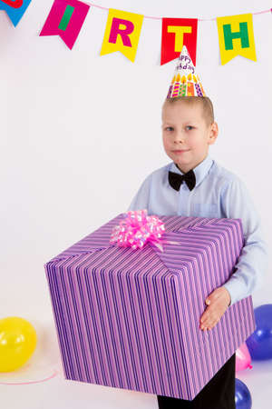 The boy holds in his hands a big box with a gift. Garland with the Inscription happy birthday.