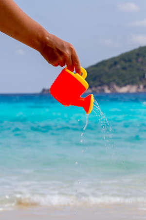 Female hand pours water from a childrens plastic watering can. Andaman sea, Similan Islands