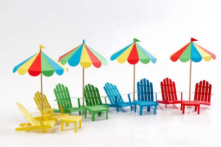 Paper beach umbrellas and chair on a white background. Isolated background.