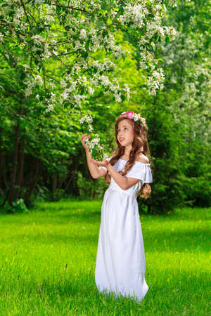 Charming girl in a blooming Apple orchard on a Sunny spring day