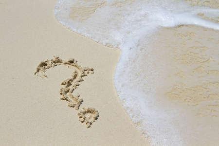 question mark sign handwritten in sand beach
